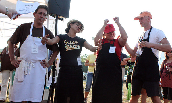 MARIA UMINSKI/Gloucester Daily Times. Julie Ann Geary, of Classic Cooks, celebrates with her teammate Travis Grandin after defeating Linda Sands and Sandro Carvalho of Sugar Magnolias, keeping her title as Seafood Throwdown Champion at the Fourth-Annual Cape Ann Farmer's Market Seafood Throwdown.