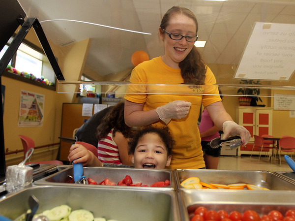 ALLEGRA BOVERMAN/Staff photo. Gloucester Daily Times. Gloucester: Kelly LeBlanc, right, the Summer Lunch coordinator at The Open Door, helps Miguel Tejada, 2, with getting fresh fruits to go with his lunch at the center on Thursday.