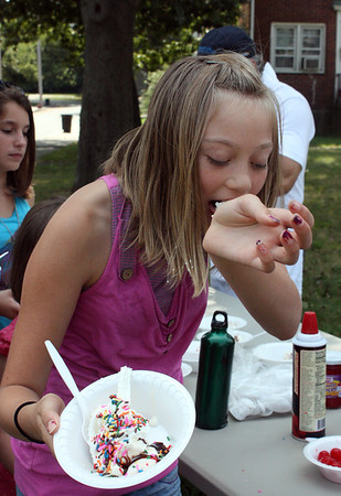 MARIA UMINSKI/Gloucester Daily Times. Emily Briere, 11 of Gloucester, licks whipped cream remnants off of her arm at the Back to School lunchtime party with Open Door at Riverdale Park. This party brought to a close the Open Door Summer Lunch Program.
