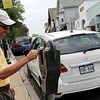 ALLEGRA BOVERMAN/Staff photo. Gloucester Daily Times. Rockport: Robert Brunet of Montreal, Canada, puts more coins in his meter along Main Street on Wednesday afternoon. He and his wife are on their fifth trip to Rockport, a place they love to visit.