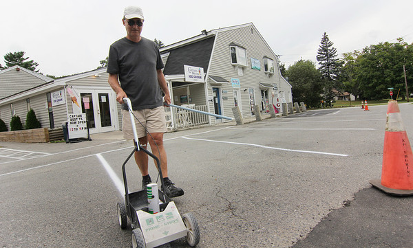 ALLEGRA BOVERMAN/Staff photo. Gloucester Daily Times.Essex: Bob Marquis of Essex paints new lines on his parking lot at Schooners Marketplace in Essex on Tuesday afternoon. He is the landlord there and does all the maintenance for the site.
