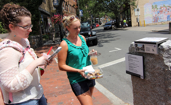 ALLEGRA BOVERMAN/Staff photo. Gloucester Daily Times. Gloucester: Abigail Adams, left, of Beverly and Elisabeth Roy of Peabody examine one of the markers along Main Street that is part of the new Harbor Walk. There is a pasta recipe featured at this stop.