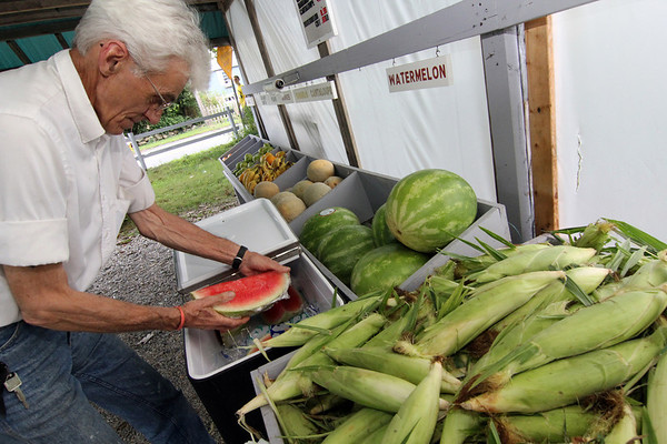 ALLEGRA BOVERMAN/Gloucester Daily Times Ralph Sweet of Lattof Farm in Rockport replenishes his supply of freshly quartered watermelon at his stand on Tuesday afternoon.