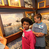 "ALLEGRA BOVERMAN/Staff photo. Gloucester Daily Times. Rockport: Pathways for Children participants who are part of the Pathways Art Club visited the studio of Rockport artist Ken Knowles on Tuesday morning. From left to right are: Malora Corrao, 9, Josh Fuller, 9, and Andrew Magnarelli, 9, looking and talking about a painting of Pavilion Beach and the Birdseye building in Gloucester by Knowles. The children were also viewing Knowles' Parsons table that he painted for the ""A Place at The Table"" Gala in November."