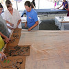 "ALLEGRA BOVERMAN/Gloucester Daily Times. Collograph workshops participants Iona Murray-Brown, Katherine Dench, Melanie Murray-Brown and Lindsay Greimann work together to decide how they'll print seaweed patterned plates onto yards of silk chiffon and organza material on Wednesday. Lanesville artist Camilla MacFadyen held a two-day workshop at Maritime Gloucester about collograph printmaking. Students collected seaweed at the pier in back of the museum, made plates by gluing the seaweed to cardboard pieces, like the ones shown here, and applied fabric paint to the three-dimensional surface to print onto dozens of yards of silk chiffon and organza to make a collaborative art installation piece for the museum. The museum also provided fish to create prints from onto fabric and stuffed fish were sewed to swim in the silky virtual aquarium of seaweed images. A ""Stock the Tank"" party that highlighted the group art piece was held on August 18, and the installation will be on view for the rest of the month at Maritime Gloucester. See their website for museum hours at <a href=""http://maritimegloucester.org/"">http://maritimegloucester.org/</a>"