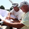 MARIA UMINSKI/Gloucester Daily Times James Padre and John Strong of Padre Construction look over plans for the Lupine Lane Housing Development in Gloucester as construction begins on the houses.