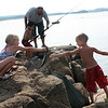 MARIA UMINSKI/Gloucester Daily Times. Brooke Matook, 5 of Essex, jokingly hands her brother, Mark Matook, 7 of Essex, a whole macrel to use as bait for his line while fishing up at Conomo Point in Essex.