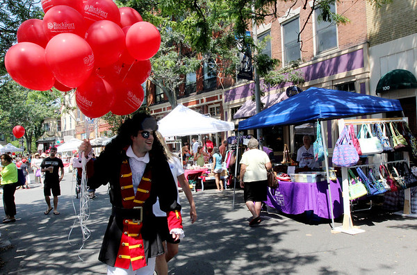 ALLEGRA BOVERMAN/Staff photo. Gloucester Daily Times. Gloucester: Jonathan Arnold of Rockport, and a Rockport Savings Bank employee, strolls along Main Street giving out  balloons on Thursday during the first day of Sidewalk Days downtown.