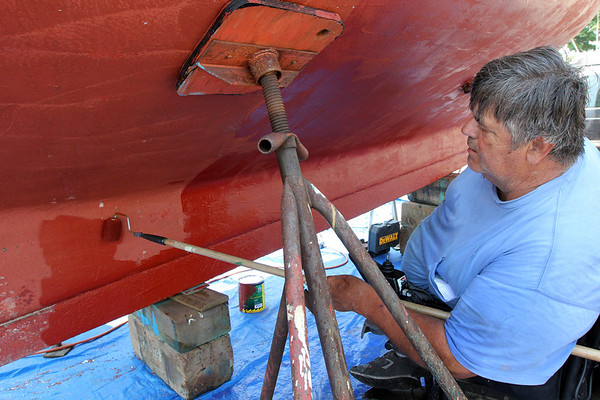 ALLEGRA BOVERMAN/Staff photo. Gloucester Daily Times. Gloucester: Ed Boynton is busy repainting his boat at Rose Marine in Gloucester.
