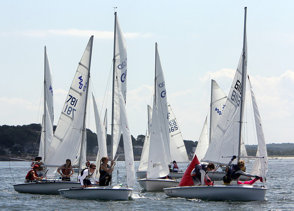 ALLEGRA BOVERMAN/Gloucester Daily Times Participants in the 420 Champions race raise their spinnakers as they saiol around a float along their race route off Wingaersheek Beach on Monday. The Annisquam Yacht Club is hosting the three-day-long Junior Olympic Sailing Festival.