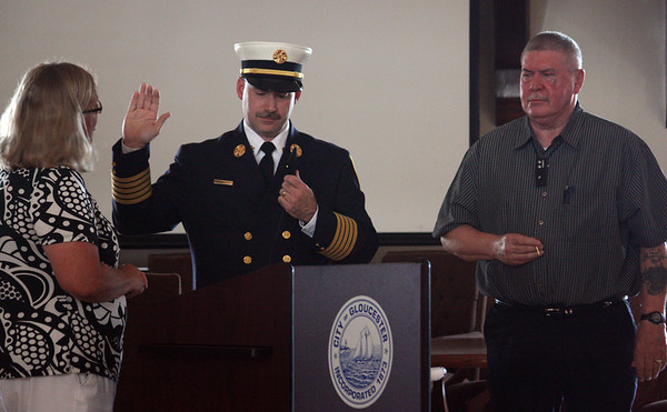 MARIA UMINSKI/Gloucester Daily Times. Mayor Carolyn Kirk swears in new Fire Chief Eric Smith at the Public Safety Badge Ceremony at Gloucester Town Hall as his father, Ralph Smith, watches on.