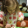 MARIA UMINSKI/Gloucester Daily Times. Six-year-old Faith Castellucci of Gloucester decorates her cupcake during the Sweet Dreams Tea Party at the Sawyer Free Library.
