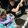 "ALLEGRA BOVERMAN/Staff photo. Gloucester Daily Times. Gloucester: Sofia Machado, 8, works with magician Evan Northrup to perform a card trick with panache and a good story during a magic skills workshop at the Gloucester Stage Company's Youth Acting Workshop on Friday. Northrup trained the actors who performed ""Carnival"" there in magic skills. He taught them card tricks, coin tricks, napkin tricks, and other magic secrets."