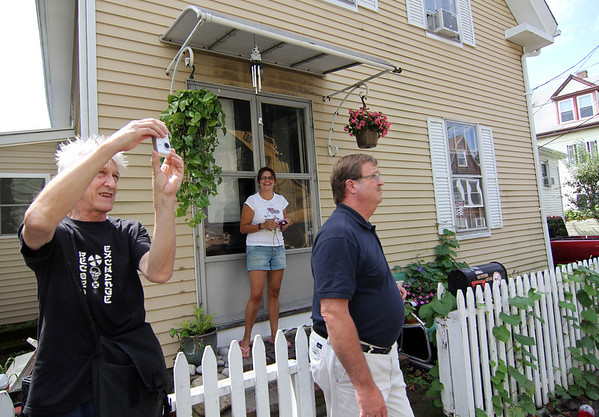 "ALLEGRA BOVERMAN/Staff photo. Gloucester Daily Times.  Musician and artist Willie ""Loco"" Alexander, who lives on School Street, perpendicular to Columbia Street in Gloucester,  Luisa Scola, center, who lives across the street, and city building inspector Bill Sandford, right, watch the demolition of 12 Columbia Street on Thursday morning."