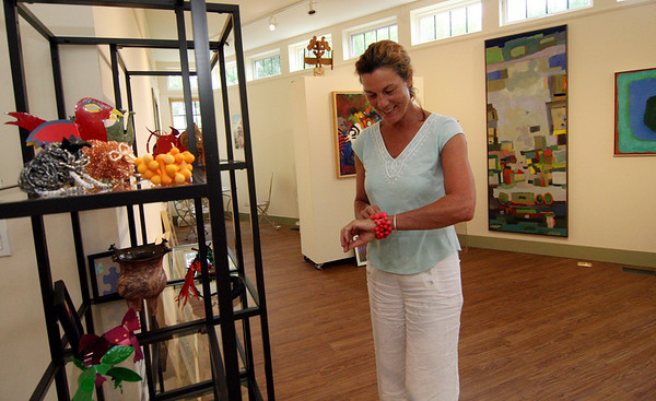 ALLEGRA BOVERMAN/Gloucester Daily Times Cynthia Switzer Roth tries on a bracelet on display in the newly renovated and rebuilt Flatrocks Gallery in Lanesville. The gallery officially opens this weekend.