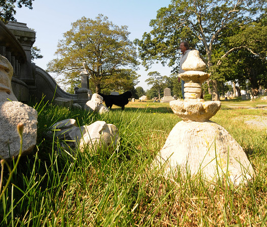 JIm Vaiknoras/Gloucester Daily Times. The tops of pillers from the monument to Eugene Wetherell sit on the ground at the Oak Grove Cemetary in Gloucester after it was damaged by vandals.