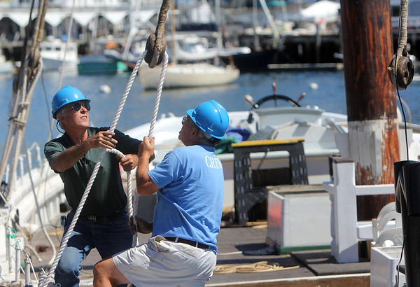 ALLEGRA BOVERMAN/Gloucester Daily Times The Schooner Adventure's masts were reinstalled on Wednesday morning at the Gloucester Marine Railways. Board member Greg Bover, left, and ship's keeper Bill Holmes work to secure one of the masts into a completely upright position.