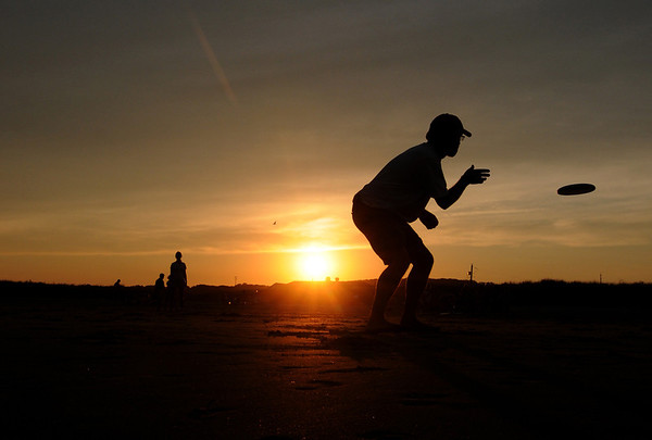 Jim Vaiknoras/Gloucester Daily Times: Jannik Jelmberg of Rockport catches a frizbee as the sunsets on Good Harbor Beach in Gloucester Wednesday night.