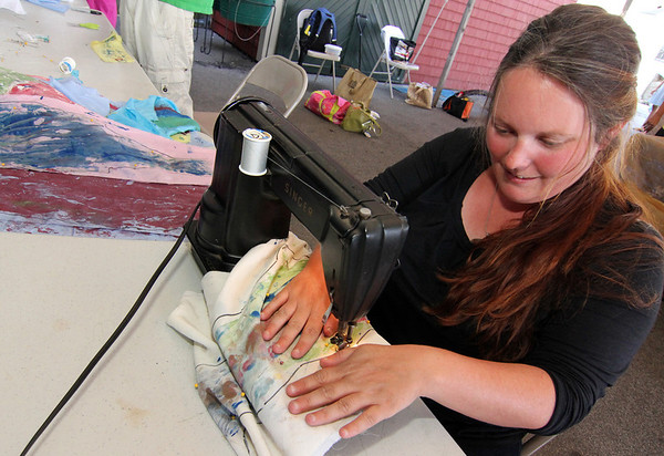 """ALLEGRA BOVERMAN/Gloucester Daily Times. Maritime Gloucester education director Mary Kay Taylor sews fabric printed with local fish images into stuffed fish during a collograph workshop held there. Lanesville artist Camilla MacFadyen held the  two-day workshop at Maritime Gloucester about collograph printmaking. Students collected seaweed at the pier in back of the museum, made plates by gluing the seaweed to cardboard pieces and applied fabric paint to the three-dimensional surface to print onto dozens of yards of silk chiffon and organza to make a collaborative art installation piece for the museum. The museum also provided fish to create prints from onto fabric and stuffed fish were sewn to swim in the silky virtual aquarium of seaweed images. A """"Stock the Tank"""" party that highlighted the group art piece was held on August 18, and the installation will be on view for the rest of the month at Maritime Gloucester. See their website for museum hours at <a href=""""http://maritimegloucester.org/"""">http://maritimegloucester.org/</a>"""