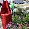 "ALLEGRA BOVERMAN/Staff photo. Gloucester Daily Times. Gloucester: Jay Ramsey of Essex, and of Farm Creek Landscaping, tends one of six perennial gardens designed along the new Harbor Walk. This one is next to Gloucester House, in the John ""Gus"" Foote Park. The marker nearby is titled ""Fishing today."""