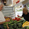 ALLEGRA BOVERMAN/Gloucester Daily Times Ralph Sweet of Lattof Farm in Rockport, left, chats with Pat Brown of Rockport, right, as she selects the perfect tomato at his stand on Tuesday afternoon. She buys produce from him daily.