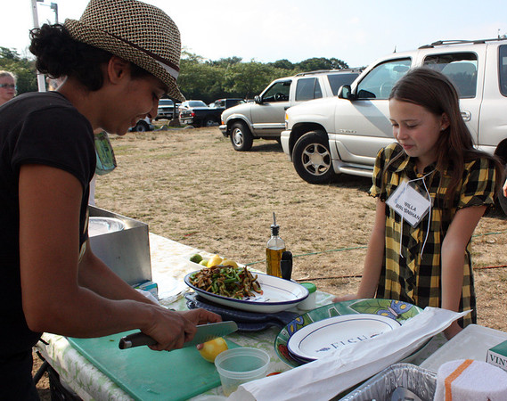 MARIA UMINSKI/Gloucester Daily Times. Nine-year-old Willa Brosnihan, one of three kid judges on the judging pannel, watches Linda Sands of Sugar Magnolias as she prepare's her dish for the fourth-annual Cape Ann Farmer's Market Seafood Throwdown.