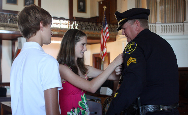 """MARIA UMINSKI/Gloucester Daily Times. Twins Melanie and Alex MacDonald present their father Eugene """"Sandy"""" MacDonald with a pin representing his premotion to Sergeant with the Gloucester Police Department."""
