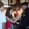 "MARIA UMINSKI/Gloucester Daily Times. Twins Melanie and Alex MacDonald present their father Eugene ""Sandy"" MacDonald with a pin representing his premotion to Sergeant with the Gloucester Police Department."