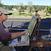 ALLEGRA BOVERMAN/Gloucester Daily Times Judy Greulich of Wakefield was painting along the side of the road in Essex on Wednesday and was going to return, if good weather, on Thursday, to paint the scene at Bothways Farm.