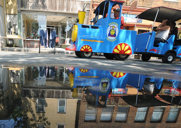 Gloucester:The Roaming Railroad carries it's carges down a amin Street in Gloucester past a puddle caused by Wednesday nights rain during the 54th annual Gloucester Sidewalk Bazaar. Jim Vaiknoras/staff photo