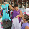 ALLEGRA BOVERMAN/Staff photo. Gloucester Daily Times. Gloucester: Kristen Rideout, left, of Gloucester, looks at clothing for her daughters outside Kids Unlimited on Main Street on Thursday during the Sidewalk Days event. Her daughter Erin, 6, is at right.