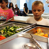 MARIA UMINSKI/Gloucester Daily Times. Six-year-old Ronald Todd of Gloucester surveys the spread of vegetables and fruits in the new salad bar at Riverdale Park sponsored by the Open Door Summer Lunch Program. The Open Door Summer Lunch Program will end its season with a Back To School Lunch Party at Riverdale Park on Friday August 24th from 11:30am- 1pm.