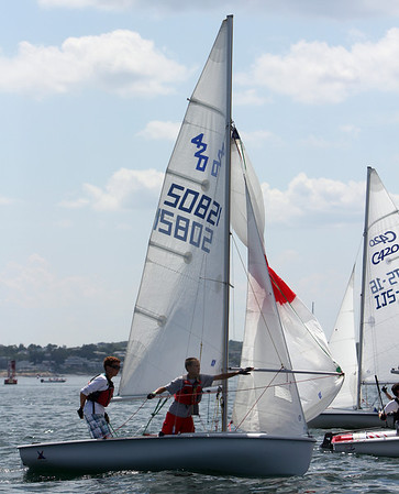 ALLEGRA BOVERMAN/Staff photo. Gloucester Daily Times. Adam Piispanen, left, and Sam Denney  of Annisquam Yacht Club start hoising their spinnaker as they go around a float during the 420 Champions race off Wingaersheek Beach on Monday. The AYC is hosting the three-day-long Junior Olympic Sailing Festival.
