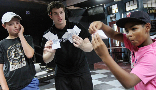 """ALLEGRA BOVERMAN/Staff photo. Gloucester Daily Times. Gloucester: <br /> Mark Turner, 12, left, and Brandon Bruce, 11, right, work with magician Evan Northrup to perform a card trick with panache and a good story during a magic skills workshop at the Gloucester Stage Company's Youth Acting Workshop on Friday. Northrup trained the actors who performed """"Carnival"""" there in magic skills. He taught them card tricks, napkin tricks, coin tricks  and other magic secrets."""