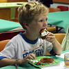 MARIA UMINSKI/Gloucester Daily Times. Seven-year-old Deston Cauthers takes a big bite of his decorated cupcake during the Sweet Dreams Tea Party at the Sawyer Free Library.