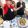 MARIA UMINSKI/Gloucester Daily Times. Julie Ann Geary, of Classic Cooks, explains her dish to the hungry crowd, at the fourth-annual Cape Ann Farmer's Market Seafood Throwdown. Both teams had to incorporate Ocean Perch into their dishes, which was mystery fish ingredient.
