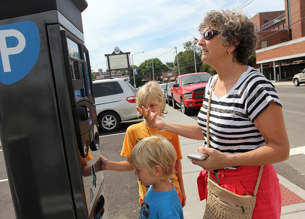 ALLEGRA BOVERMAN/Gloucester Daily Times. Marilyn Ott of  Venice, Fla., and her grandsons Luc, center, and Timon Hallisey, of Easthampton, were going to eat downtown on Wednesday but had to use the municipal parking kiosk in front of the Gloucester House first. Ott had trouble using her credit card in it on the first day of the kiosks being in service.