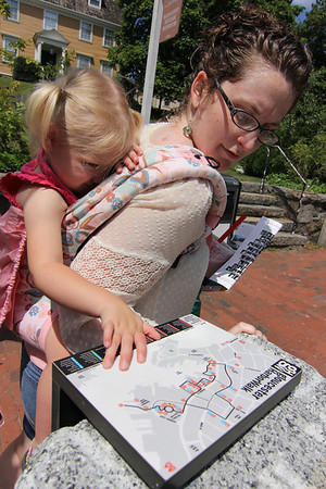 ALLEGRA BOVERMAN/Staff photo. Gloucester Daily Times. Gloucester: Abigail Adams, right, of Beverly, and her daughter Isabelle Adams-Kunzer, 2, take a look on Monday at one of the markers along Main Street that is part of the new HarborWalk.