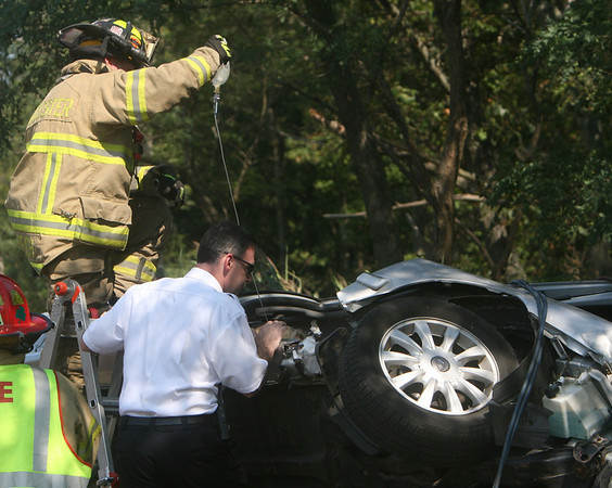 ALLEGRA BOVERMAN/Gloucester Daily Times Gloucester firefighters work to extricate a woman trapped in her car on Thursday afternoon following a crash along Route 128 North near Exit 14. She was taken to Tufts Medical Center by helicopter for treatment. Fire chief Eric Smith, right, speaks with the victim.