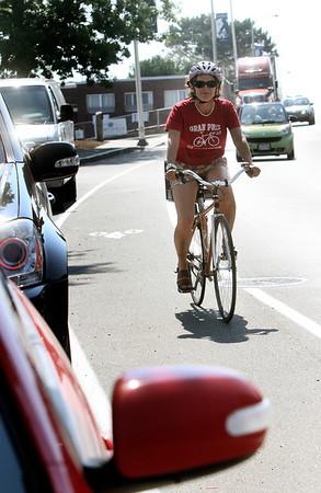 ANGIE BEAULIEU/Staff photo. Cyclist Heidi Wakeman uses a new bike lane along Rogers Street. 08/21/13