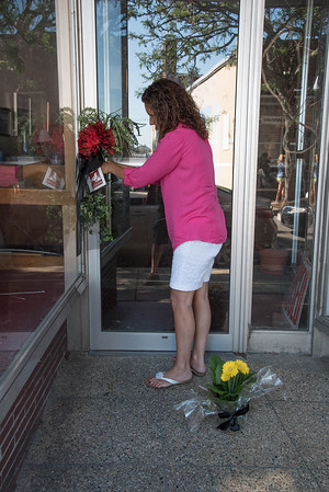 Desi Smith/Staff Photo.    Felicia Ciaramitaro Mohan places a bouquet of flowers on the door of Photographer Fred Boden's store front on Main Strret Friday afternoon, as a small memorial starts to grow after his passing.     August 28,2015