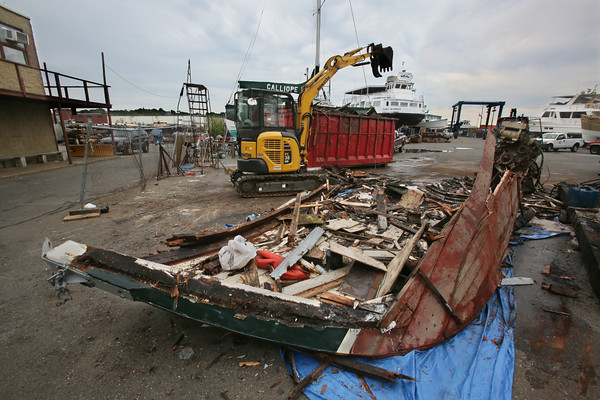 MIKE SPRINGER/Staff photo<br /> A worker for the Gloucester Department of Public Works uses a backhoe to tear apart and dispose of the Irish Piper fishing boat Monday at Rose Marine. By late afternoon there was little left of the boat.