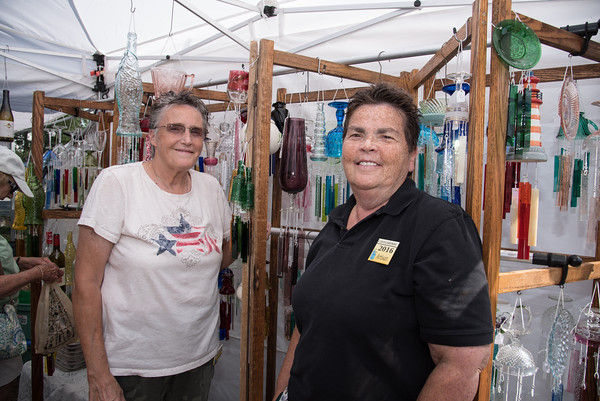 Desi Smith Photo.   From left, Deb Carrier and Ann Torrey, owners of The Crafty Peddlers located in Worcester,Ma, stand in front of their unique glass chimes at the Annual Gloucester Waterfront Festival held Saturday at Stage Fort Park.  August 20,2016