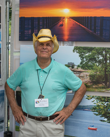 Desi Smith Photo.  Photographer Anthony Shays of The Artist with the Camera, from Plymptom,Ma, stands in front of his work that was on displsy at the Annual Gloucester Waterfront Festival held Saturday at Stage Fort Park.  August 20,2016