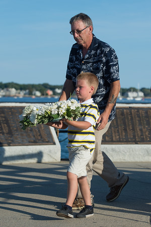 """Desi Smith Photo.  Wallace Gray III 6, walks with his grandfather Wallace Gray of Gloucester to place a wreath at the Fishermens Monument remembering his father Wallce """"Chubby"""" Gray Jr who lost his life aboard the Foxy Lady II 2012, at the Annual Gloucester Fishermen's Memorial Service held Saturday afternoon on Stacey Boulevard.     August 27,2016."""