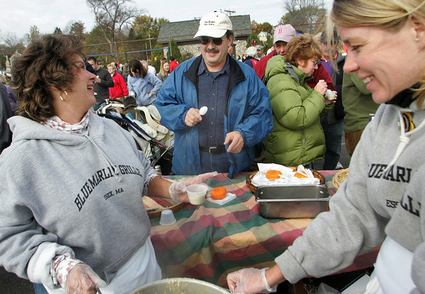 Essex: Gisela Mattson, left, hands Paul LeBrasseur some chowder from the the Blue Marlin Grille table at the Essex Clam Fest Saturday.  Over a dozen restaurants gave out sample of their chowder to the hundreds of people who waited in long lines for a taste. Alos pictured is Christine MacDonald, right, of Bue Marlin Grille.  Mary Muckenhoupt/Gloucester Daily Times<br /> /, Essex: Gisela Mattson, left, hands Paul LeBrasseur some chowder from the the Blue Marlin Grille table at the Essex Clam Fest Saturday.  Over a dozen restaurants gave out sample of their chowder to the hundreds of people who waited in long lines for a taste. Alos pictured is Christine MacDonald, right, of Bue Marlin Grille.  Mary Muckenhoupt/Gloucester Daily Times<br /> /
