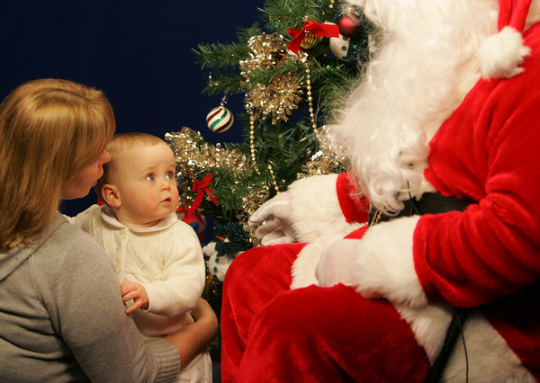 Gloucester: Sopia Parsons, 1 year, stays close to her grandmother Carol Thompson as she visits with Santa at the Cape Ann TV studio Friday afternoon.  Children of Cape Ann were invited to meet Santa at the studio so their meeting would be taped and air on Christmas Eve and Christmas Day. Mary Muckenhoupt/Gloucester Daily Times