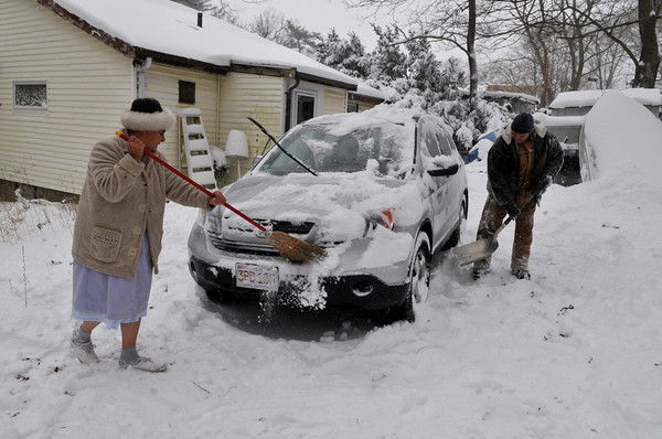 Gloucester: David White helps his mother-n-Law  Edie Smith clean off the snow on her car sunday afternoon on Clearveiw Ave. Desi Smith Photo/Gloucester Daily Times. December 20,2009.