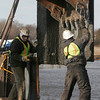 Essex: Bill Gyman and Sean White of Atlantic Support Installation hook steel barrier in place to form a dam along the Causeway to catch debris from the construction project. Photo by Kate Glass/Gloucester Daily Times