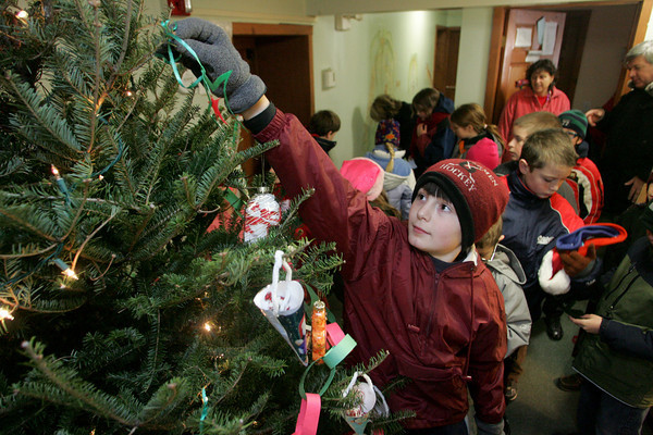 Gloucester: James Turners, a sixth grader at the Eastern Point Day School, hangs an ornamanet on the Christmas tree the school delivered to the TCB House Friday morning.  Every year the Easter Point Day school delivers a tree from the school's lobby and christmas presents from the students to the TCB, Taking Care of Business, House which is a home for families in transistion located just down the street form the Eastern Point Day School.  The school also donates two turkey dinners for the families to have on Christmas. Mary Muckenhoupt/Gloucester Daily Times
